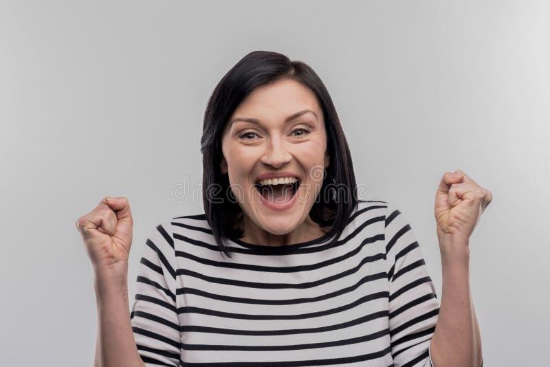 Interno de cabelo escuro que sente feliz após ter lido a letra de aceitação fotografia de stock royalty free