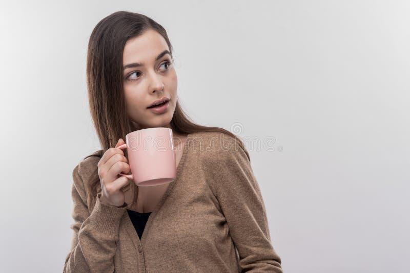 interno de sexo femenino Oscuro-cabelludo que tiene resto mientras que bebe el café durante tiempo del almuerzo imagen de archivo libre de regalías