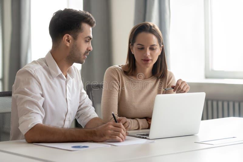 Interno de sexo masculino de enseñanza del colega del mentor que habla femenino que mira el ordenador portátil fotos de archivo