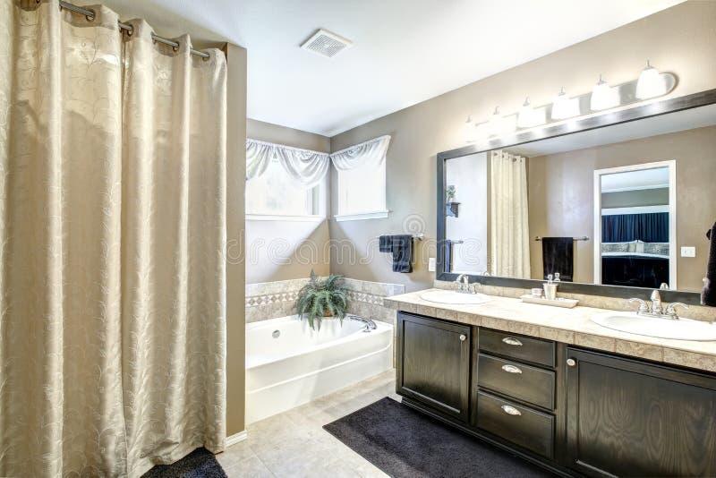 Interno del bagno con il gabinetto nero ed il grande specchio immagine stock libera da diritti