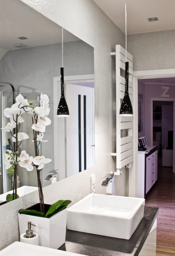 Interno del bagno elegante con il grande fiore dell'orchidea e dello specchio fotografie stock