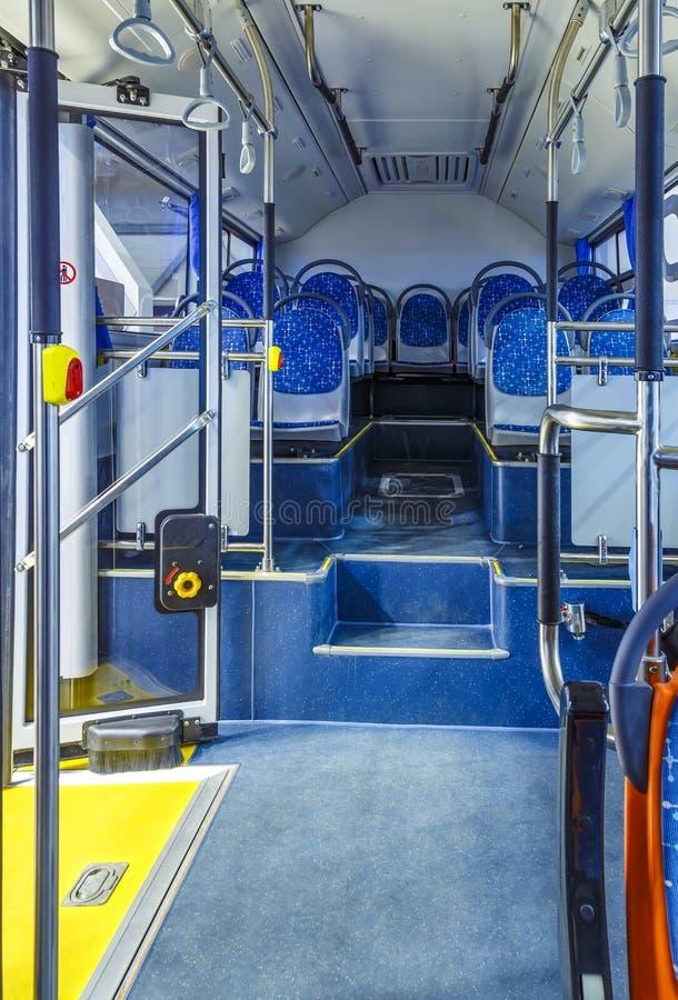 Interno del bus, interno bianco del trasporto della città con i sedili blu nella fila, posti di pensionamento, porte aperte, mani immagine stock libera da diritti