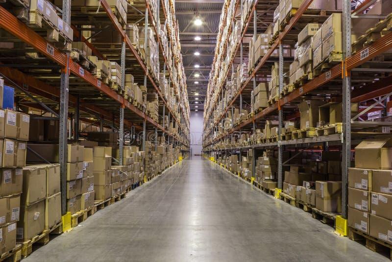 Interno del magazzino con gli scaffali pieni delle scatole immagini stock libere da diritti