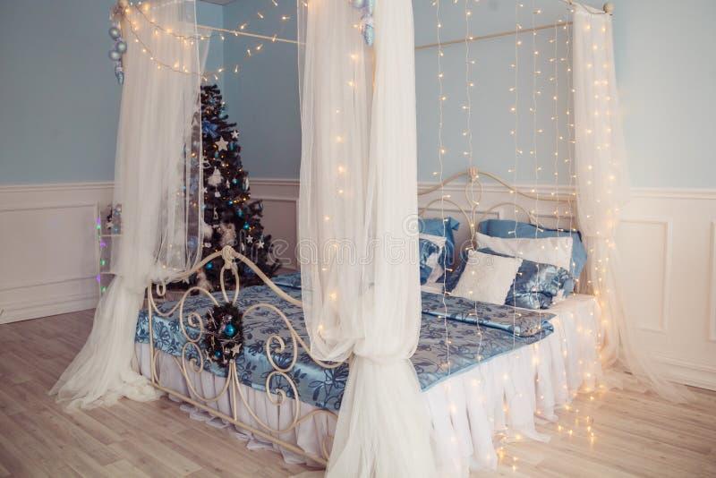 Interno del nuovo anno con il letto e l'albero di Natale De blu e bianco fotografia stock
