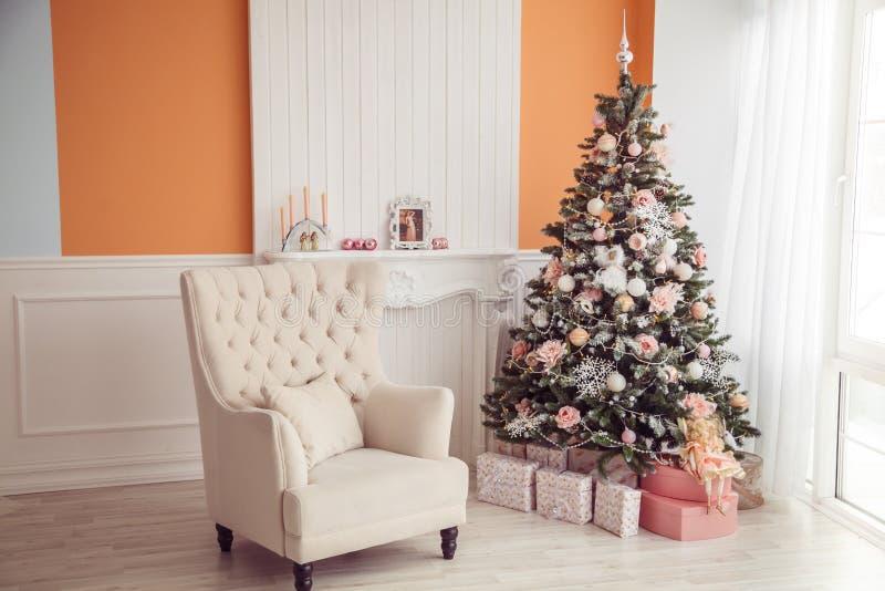 Interno del nuovo anno con l'albero di Natale e della poltrona Rosa e ora fotografia stock libera da diritti
