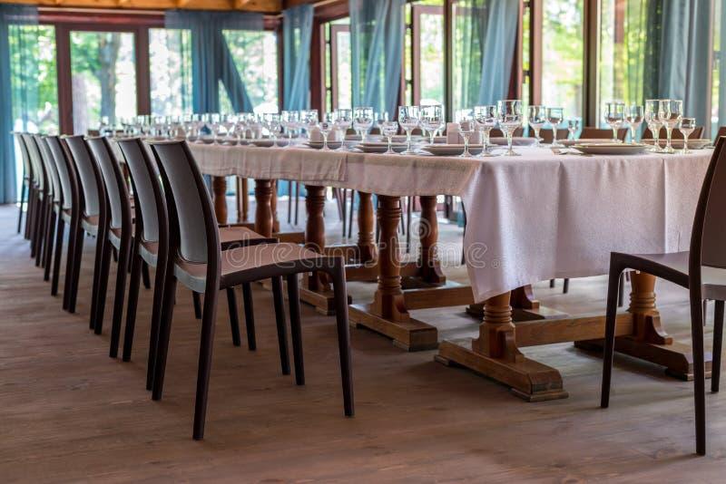 Interno del ristorante, caffè Tabelle con gli utensili, piatti, wiches, coltelli, vetri e vetri di vino e sedie di marrone, prepa fotografie stock