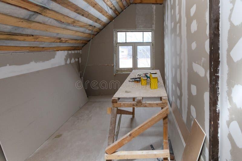 Interno dell'appartamento della stanza con la nuova finestra e l'impalcatura casalinga dei materiali, strumenti, livello durante  immagine stock
