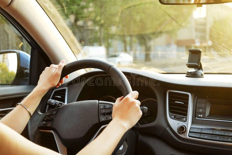 Interno dell'automobile con l'autista femminile che si siede dietro la ruota, luce molle di tramonto Cruscotto lussuoso ed elettr fotografia stock