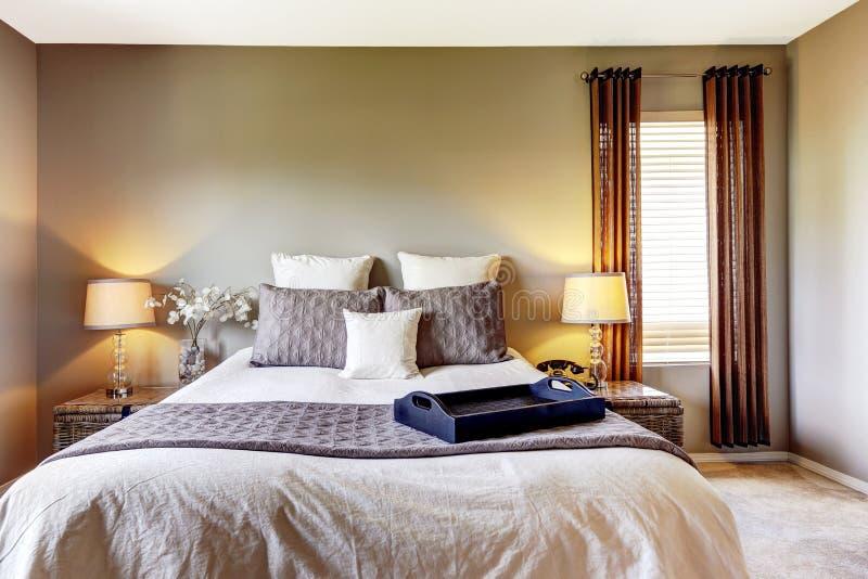 Interno della camera da letto con il pavimento di tappeto ed il grande letto immagine stock
