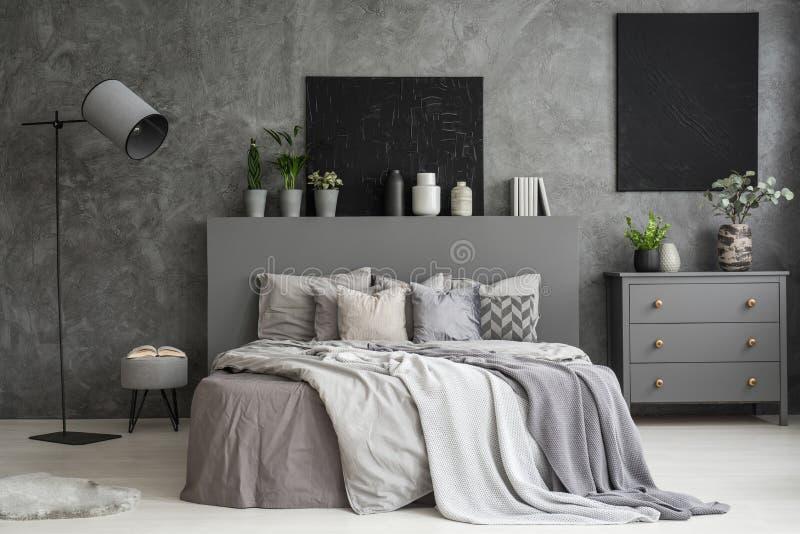 Interno della camera da letto di grey di cenere con due pitture nere sulla parete a fotografia stock libera da diritti