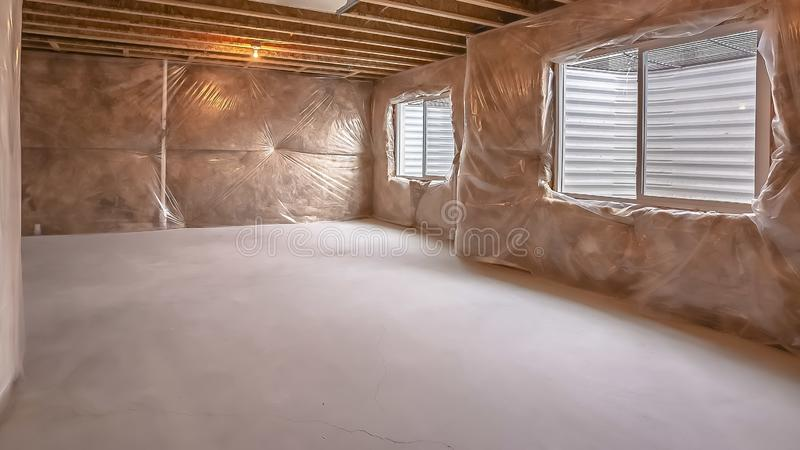 Interno della casa di panorama in costruzione con le finestre installate sulla parete coperta di plastica immagini stock libere da diritti