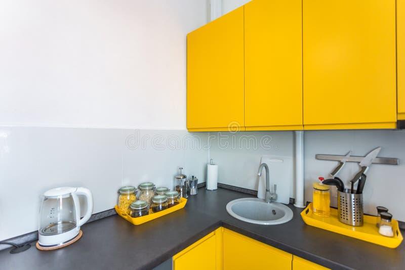 Interno della cucina moderna in appartamento piano del sottotetto nello stile minimalistic con colore giallo fotografie stock libere da diritti