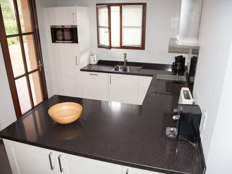 Interno della stanza della cucina con i gabinetti, l'isola di cucina ed i ripiani bianchi del granito fotografie stock