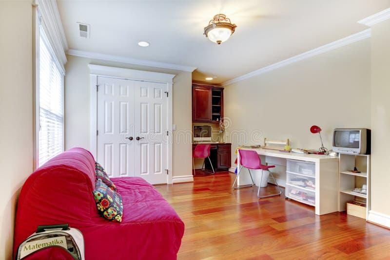 Interno della stanza del gioco dello studio a distanza dei bambini con il sofà rosa. immagini stock libere da diritti