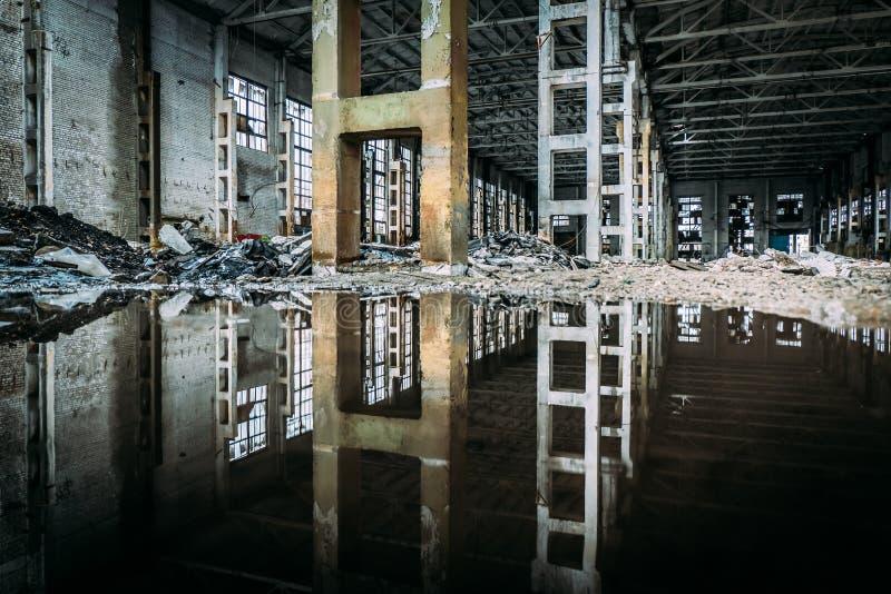 Interno di fabbricato industriale rovinato abbandonato sporco sommerso con la riflessione dell'acqua fotografia stock libera da diritti