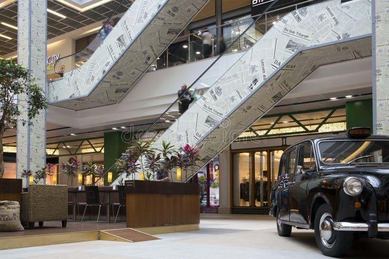 Interno di grande puttana moderna con le scale mobili, il self-service e la retro automobile esibita immagini stock