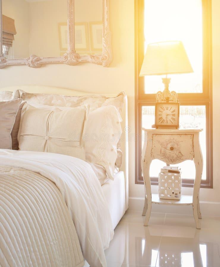 Interno di lusso della camera da letto con la lampada da tavolo e l'orologio classici di stile sul comodino fotografie stock