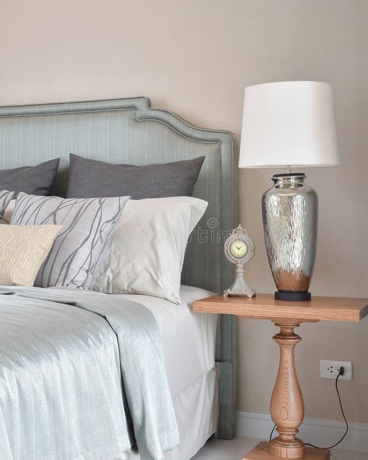 Interno di lusso della camera da letto con la lampada da tavolo e la sveglia decorative sulla tavola fotografia stock libera da diritti