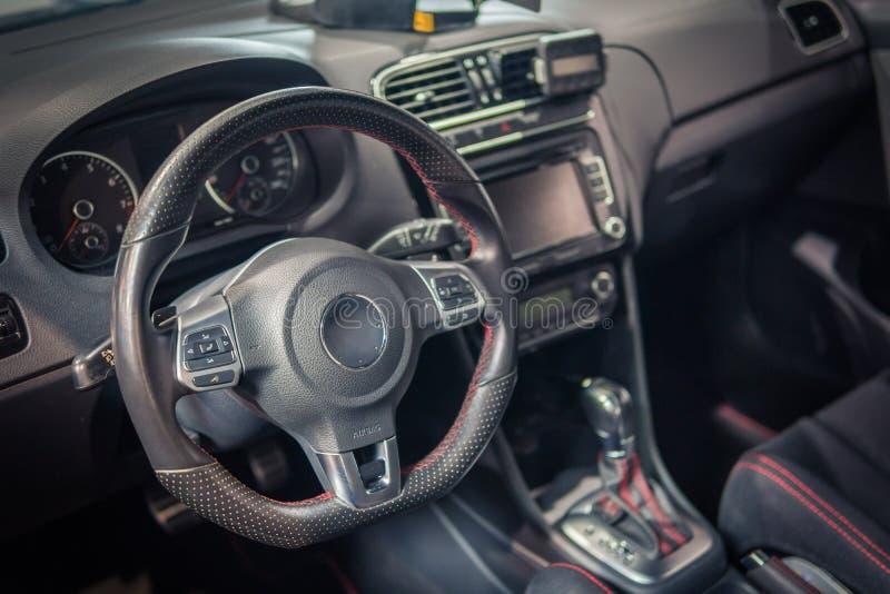 Interno di lusso scuro dell'automobile - volante, leva dello spostamento e cruscotto immagini stock
