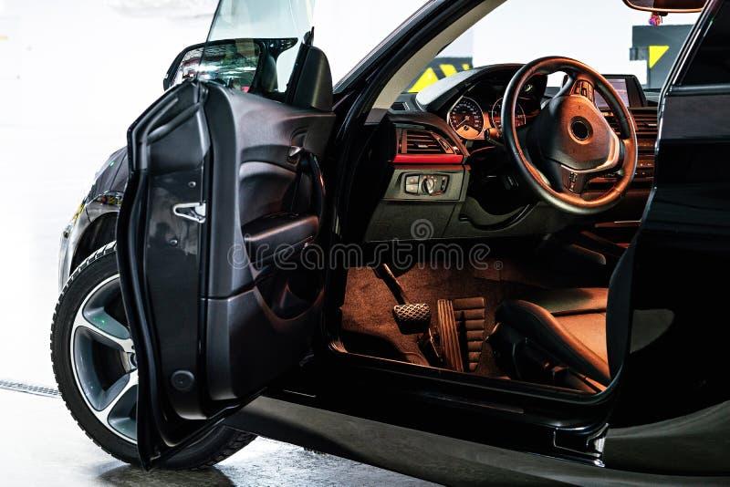 Interno di lusso scuro dell'automobile Volante, leva dello spostamento e cruscotto immagine stock libera da diritti