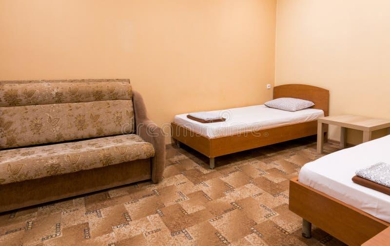 Interno di piccola stanza con un sofà e due letti immagine stock