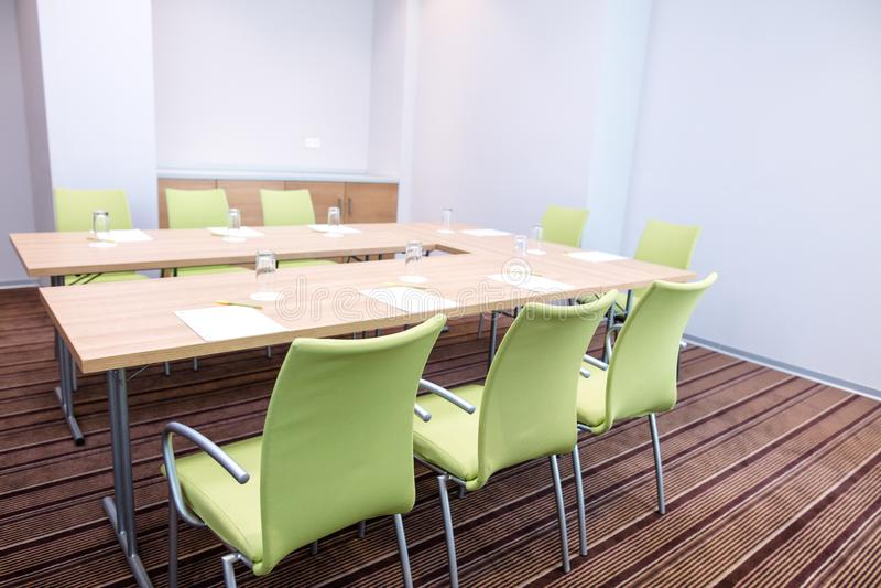 Interno di stanza leggera con le pareti blu, la tavola di legno e le sedie verdi fotografia stock