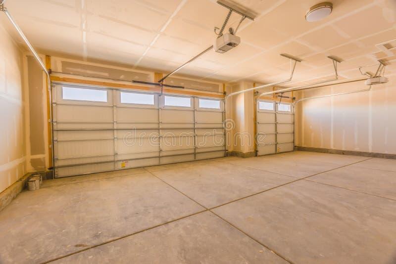 Interno di un garage non finito con le pareti ed il soffitto non dipinti immagine stock libera da diritti