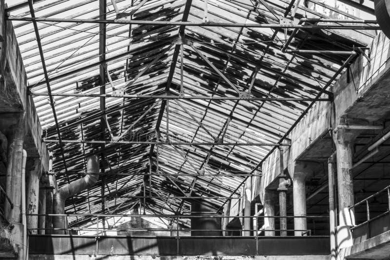 Interno di una fabbrica abbandonata in bianco e nero Il vetro rotto ed il cemento di sbriciolatura segnano una fabbrica una volta fotografia stock