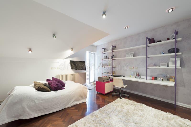 Interno di una stanza adolescente moderna in appartamento del sottotetto immagini stock libere da diritti