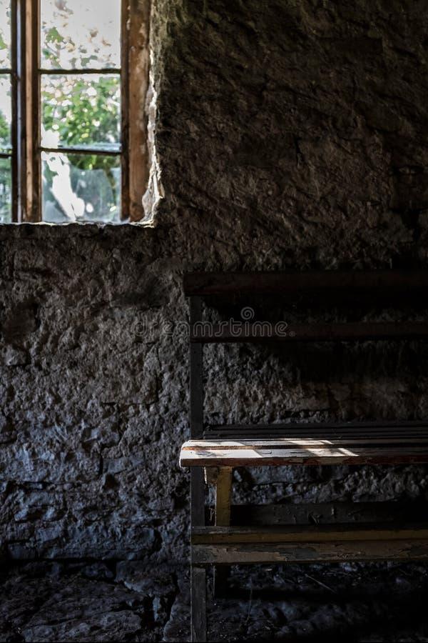 Interno di vecchia casa di pietra con una finestra e un lato del banco fatto a mano di legno fotografie stock
