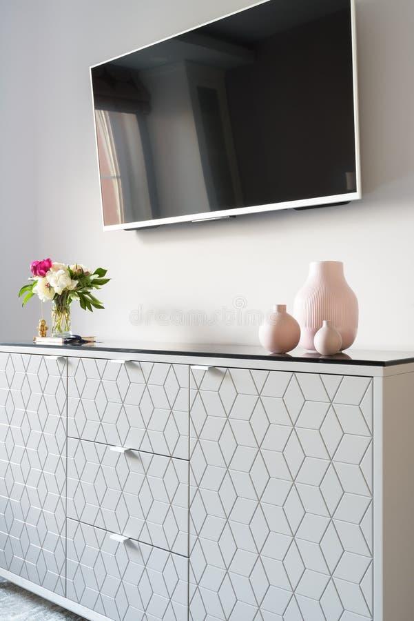 Interno domestico moderno con la TV ed i fiori immagini stock