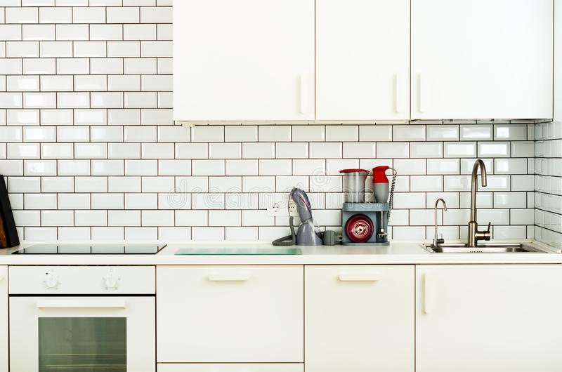 Interno e progettazione minimalistic bianchi della cucina Fondo della parete delle mattonelle Elettrodomestici - miscelatore, mac immagini stock libere da diritti