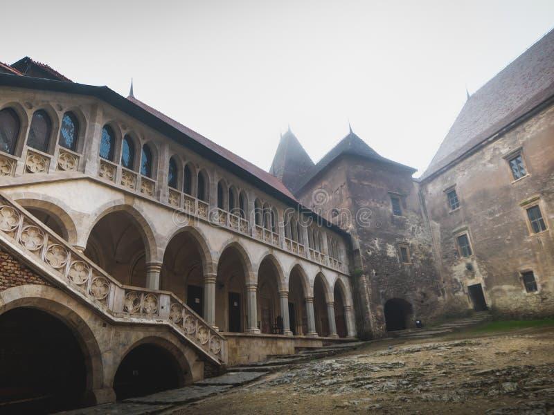Interno ed esterno del castello di Hunedoara in Romania nelle circostanze nebbiose immagine stock