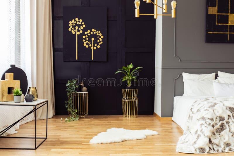 Interno grigio scuro della camera da letto con la coperta della pelliccia, accessori dell'oro, simpl immagine stock