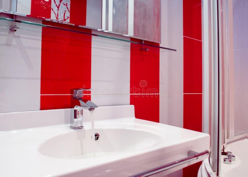 Interno luminoso del bagno nei colori rossi e bianchi fotografia stock libera da diritti