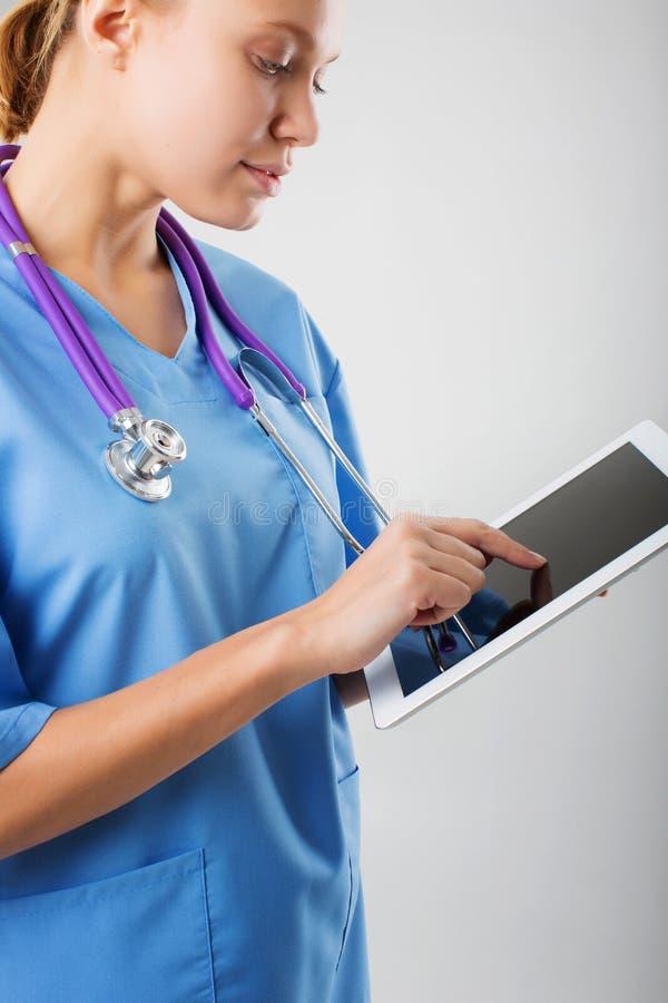 Interno médico de sexo femenino joven hermoso con la tableta foto de archivo