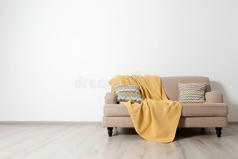 Interno minimalista del salone con il sof?, i cuscini ed il plaid vicino alla parete leggera immagini stock