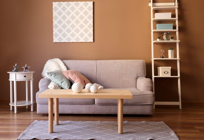 Interno moderno del salone con il sofà comodo e la tavola di legno vicino alla parete di colore immagini stock libere da diritti