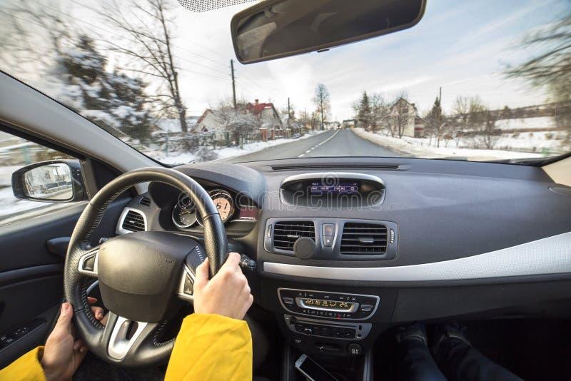 Interno moderno dell'automobile con le mani femminili dell'autista sul volante, esterno nevoso del paesaggio di inverno Concetto  fotografie stock libere da diritti