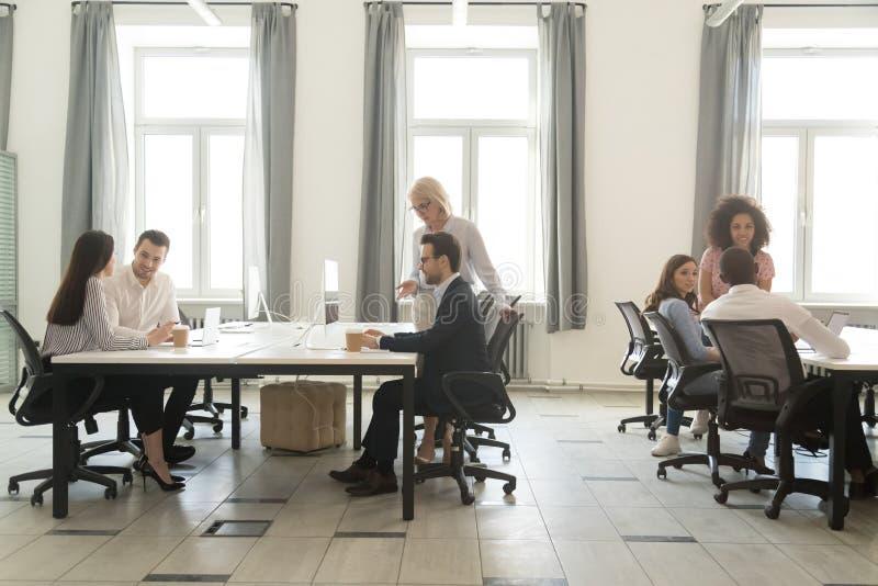 Interno moderno dell'ufficio con la gente del gruppo di affari che lavora ai computer immagini stock