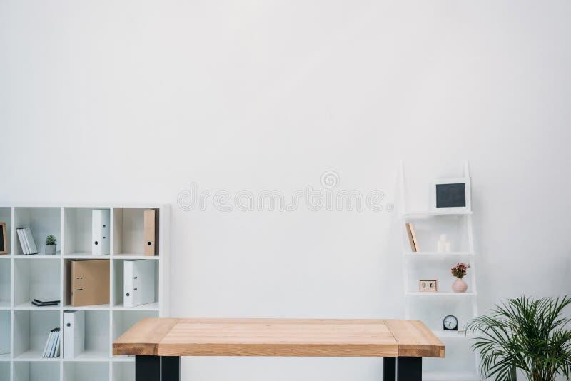 interno moderno dell'ufficio con la tavola e le cartelle di legno vuote immagine stock libera da diritti