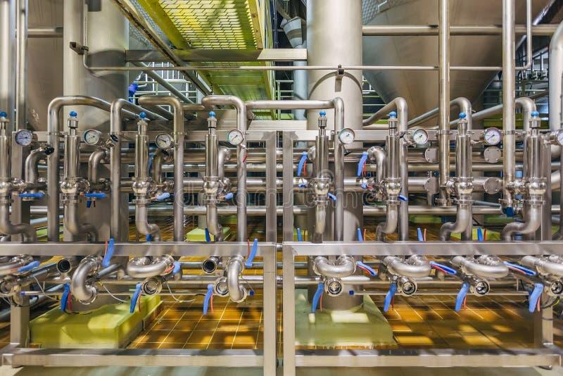 Interno moderno della fabbrica di birra I tubi industriali dell'acciaio inossidabile si sono collegati con i tini e le valvole di fotografie stock