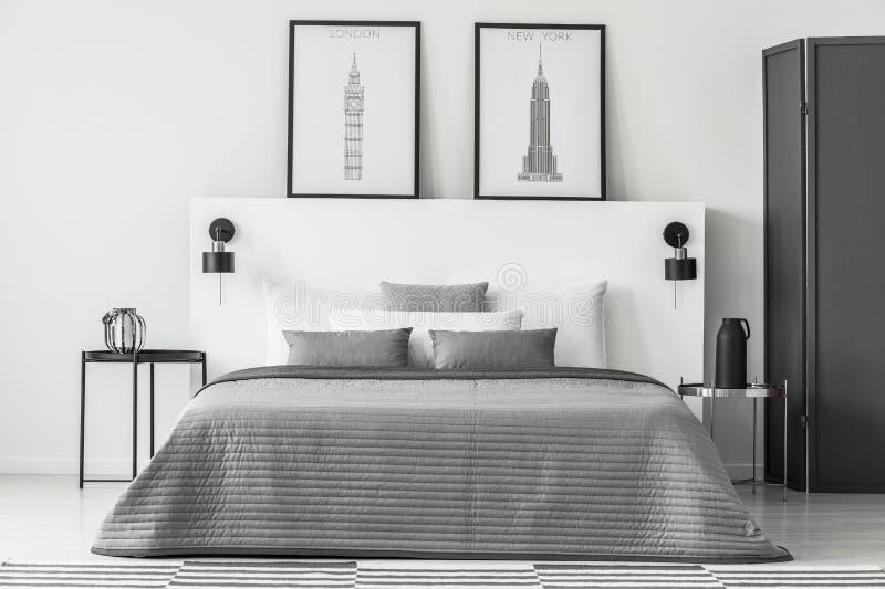 Interno monocromatico della camera da letto con i manifesti immagine stock
