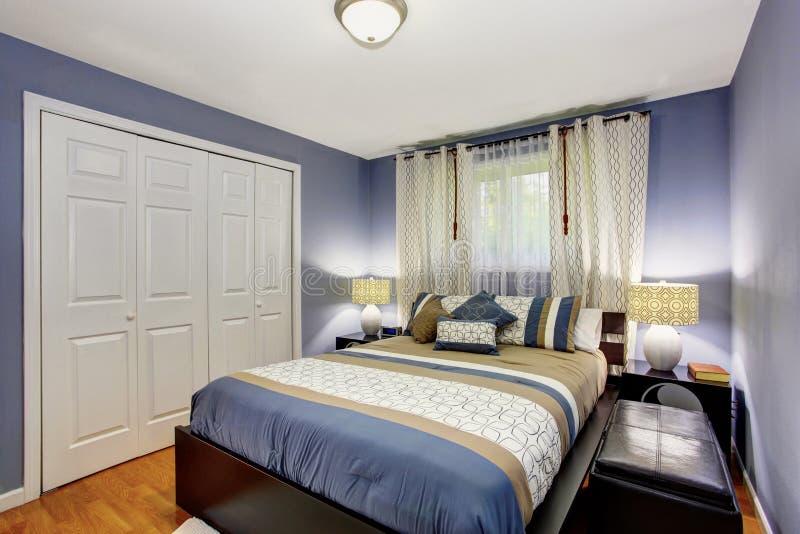 Interno nero e blu della camera da letto con il guardaroba incorporato ed il pavimento di legno duro fotografie stock