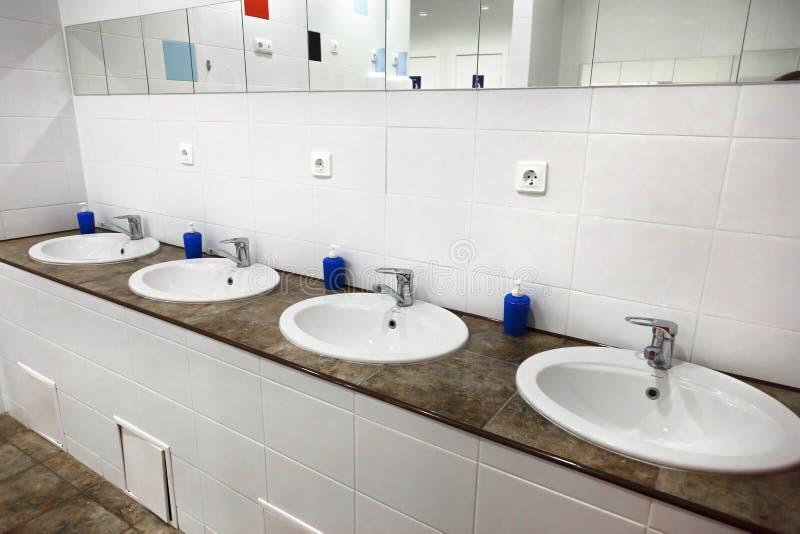 Interno pubblico del bagno degli uomini della toilette vuota con i lavandini della mano di lavaggio immagini stock