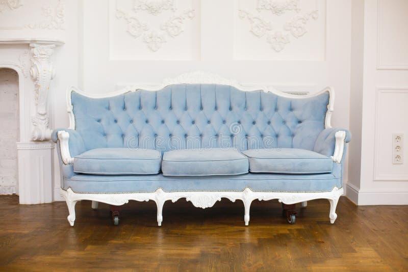 Interno reale classico leggero con il sofà molle blu con la tappezzeria del tessuto immagine stock libera da diritti