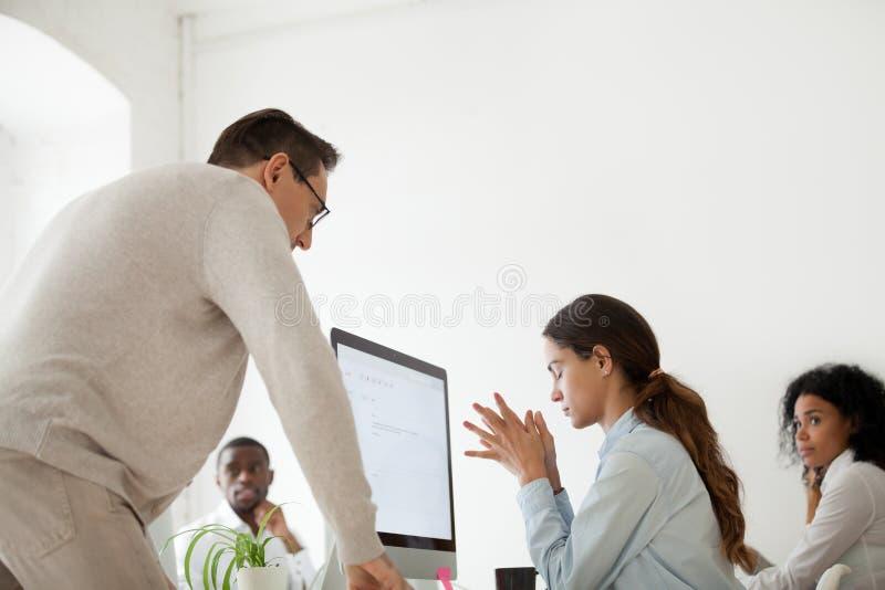 Interno rimproverante o d'infornamento del capo arrabbiato di ribaltamento in ufficio multirazziale immagine stock