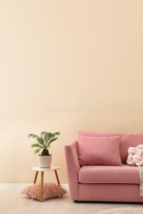 Interno semplice del salone con il sofà moderno vicino alla parete di colore immagini stock