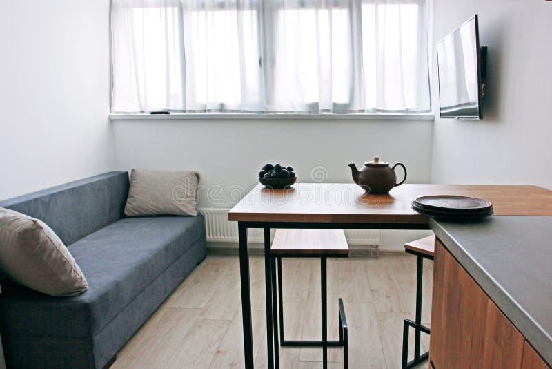 interno stile scandinava della cucina con la mobilia della quercia con una teiera dell'argilla ed i piatti, homeliness fotografia stock