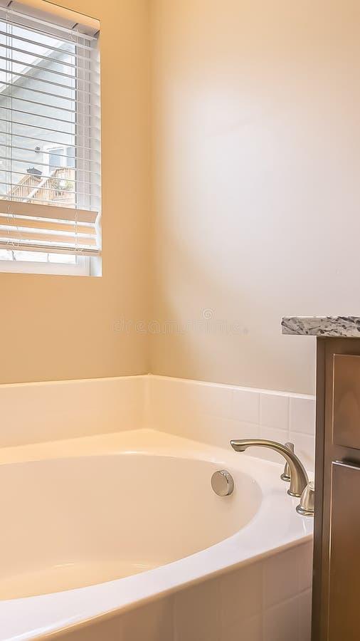 Interno verticale del bagno della struttura con la vasca ovale contro la parete e la finestra bianche con i ciechi fotografia stock